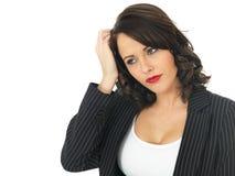Mujer de negocios joven confusa que rasguña la cabeza Fotos de archivo