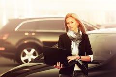 Mujer de negocios joven de moda con el ordenador portátil que se coloca al lado de su coche Imagenes de archivo