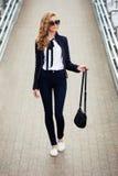 Mujer de negocios joven de moda en gafas de sol en la calle de la ciudad Fotografía de archivo libre de regalías