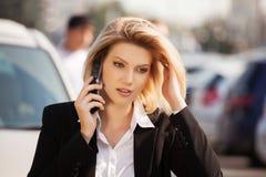 Mujer de negocios joven de moda que invita al teléfono celular Foto de archivo libre de regalías
