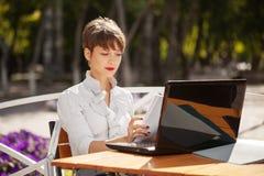 Mujer de negocios joven de moda que usa el ordenador portátil en el café de la acera Imágenes de archivo libres de regalías