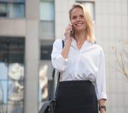 Mujer de negocios joven delante del edificio de oficinas usando su teléfono celular imágenes de archivo libres de regalías