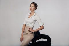 Mujer de negocios joven elegante hermosa que se coloca en el estudio con el fondo gris Imagenes de archivo
