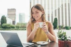 Mujer de negocios joven en el ordenador que bebe un café Fotografía de archivo libre de regalías