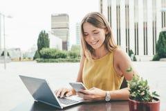 Mujer de negocios joven en el ordenador y en el teléfono móvil Fotos de archivo