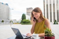 Mujer de negocios joven en el ordenador y en el teléfono móvil Fotografía de archivo libre de regalías