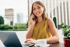 Mujer de negocios joven en el ordenador y en el teléfono móvil Imagen de archivo