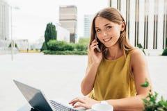 Mujer de negocios joven en el ordenador y en el teléfono móvil Foto de archivo libre de regalías
