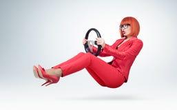 Mujer de negocios joven en el rojo y el coche con una rueda, concepto auto del conductor de los vidrios de la señora Foto de archivo libre de regalías