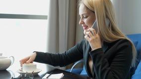Mujer de negocios joven en el traje que se sienta en la tabla en café metrajes