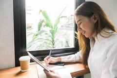 Mujer de negocios joven en el vestido blanco que se sienta en la tabla en café y que escribe en cuaderno foto de archivo libre de regalías