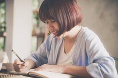Mujer de negocios joven en el vestido blanco que se sienta en la tabla en café y que escribe en cuaderno imagen de archivo
