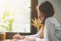 Mujer de negocios joven en el vestido blanco que se sienta en la tabla en café y que escribe en cuaderno Smartphone que habla de  Fotos de archivo libres de regalías