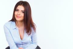 Mujer de negocios joven en la camisa azul que se sienta en la silla moderna contra blanco Fotos de archivo libres de regalías