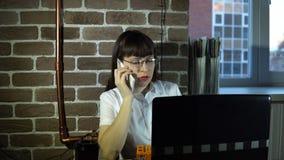 Mujer de negocios joven en la oficina con el ordenador portátil que habla en el teléfono almacen de video