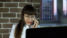 Mujer de negocios joven en la oficina con el ordenador portátil que habla en el teléfono almacen de metraje de vídeo
