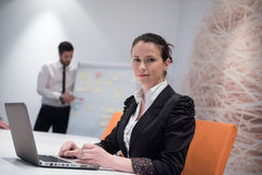 Mujer de negocios joven en la reunión usando el ordenador portátil Fotografía de archivo libre de regalías