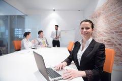 Mujer de negocios joven en la reunión usando el ordenador portátil Imágenes de archivo libres de regalías