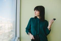 Mujer de negocios joven en una camisa oscura que se coloca en oficina moderna con el teléfono a disposición y que mira en la vent Imagen de archivo libre de regalías