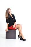 Mujer de negocios joven en una falda roja y una chaqueta negra Imagen de archivo libre de regalías
