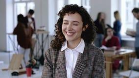 Mujer de negocios joven europea feliz que sonríe alegre en traje formal elegante con el pelo rizado, presentando en la oficina mo metrajes