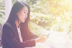 Mujer de negocios joven feliz que se sienta en el café urbano con café y que usa su teléfono elegante Foto de archivo libre de regalías