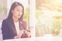 Mujer de negocios joven feliz que se sienta en el café urbano con café y que usa su teléfono elegante Imagen de archivo