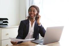 Mujer de negocios joven feliz que se sienta en el escritorio de oficina que habla en el teléfono móvil con un documento a disposi fotografía de archivo