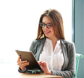 Mujer de negocios joven feliz que usa el ordenador portátil en la oficina en blanco Foto de archivo libre de regalías