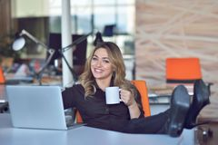 Mujer de negocios joven hermosa feliz que se sienta y que habla en el teléfono celular en oficina fotografía de archivo