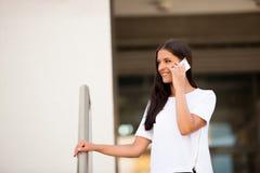 Mujer de negocios joven hermosa que camina en la calle y el talkin en s Imagen de archivo