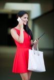 Mujer de negocios joven hermosa que camina en la calle y el talkin en s Imagen de archivo libre de regalías
