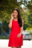 Mujer de negocios joven hermosa que camina en la calle y el talkin en s Fotografía de archivo libre de regalías