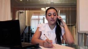 Mujer de negocios joven hermosa que habla en un teléfono móvil que discute un proyecto del negocio en una oficina que se sienta e metrajes