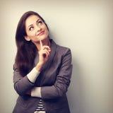 Mujer de negocios joven hermosa que piensa y que mira para arriba Foto de archivo libre de regalías