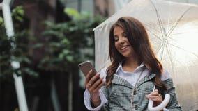 Mujer de negocios joven hermosa usando smartphone en la calle en el tiempo lluvioso, sonriendo, paraguas de la tenencia, comunica almacen de metraje de vídeo