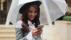 Mujer de negocios joven hermosa usando smartphone en la calle en el tiempo lluvioso, sonriendo, paraguas de la tenencia, comunica almacen de video