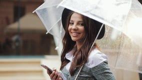Mujer de negocios joven hermosa usando smartphone en la calle en el tiempo lluvioso, sonrisa, celebrando el paraguas Ella que mir metrajes
