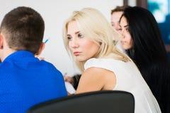 Mujer de negocios joven pensativa con un grupo de hombres de negocios Imagen de archivo