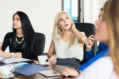 Mujer de negocios joven pensativa con un grupo de hombres de negocios Imagenes de archivo