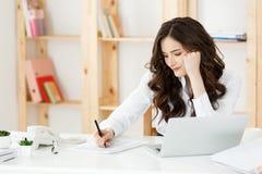 Mujer de negocios joven preocupante que trabaja con el documento en la oficina moderna imágenes de archivo libres de regalías