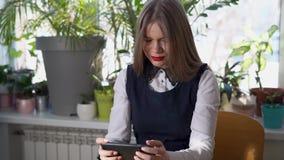 Mujer de negocios joven que busca al cliente potencial de su compañía en un smartphone almacen de metraje de vídeo