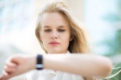 Mujer de negocios joven que comprueba el tiempo en su reloj imagen de archivo libre de regalías