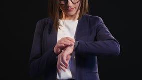 Mujer de negocios joven que comprueba el tiempo en su reloj almacen de video