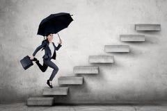 Mujer de negocios joven que corre en la escalera imagen de archivo