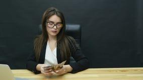 Mujer de negocios joven que cuenta el dinero almacen de metraje de vídeo