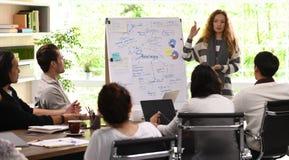 Mujer de negocios joven que da la presentación en los planes futuros imágenes de archivo libres de regalías
