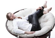 Mujer de negocios joven que descansa en una silla suave grande Foto de archivo