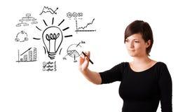 Mujer de negocios joven dibujando la bombilla con los diversos diagramas imágenes de archivo libres de regalías