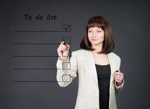 Mujer de negocios joven que enumera para hacer a la gestión de tiempo de la lista Imagen de archivo